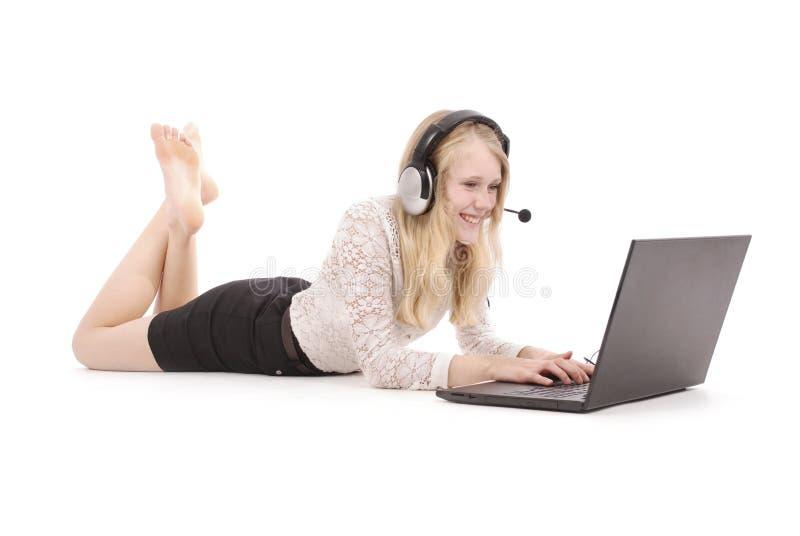 Recht junge Jugendliche mit dem Laptop und Kopfhörern, die auf dem Boden liegen lizenzfreies stockfoto