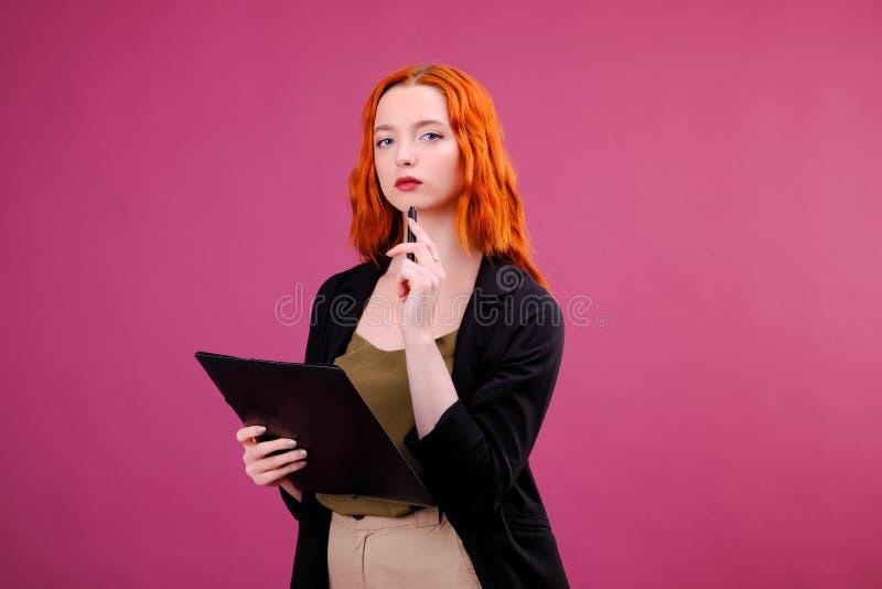Recht junge Sch?nheitsstellung, Schreiben, nehmen Anmerkungen, Holdinglehrbuchnotizbuchorganisator und Stift in die Hand lizenzfreie stockfotos