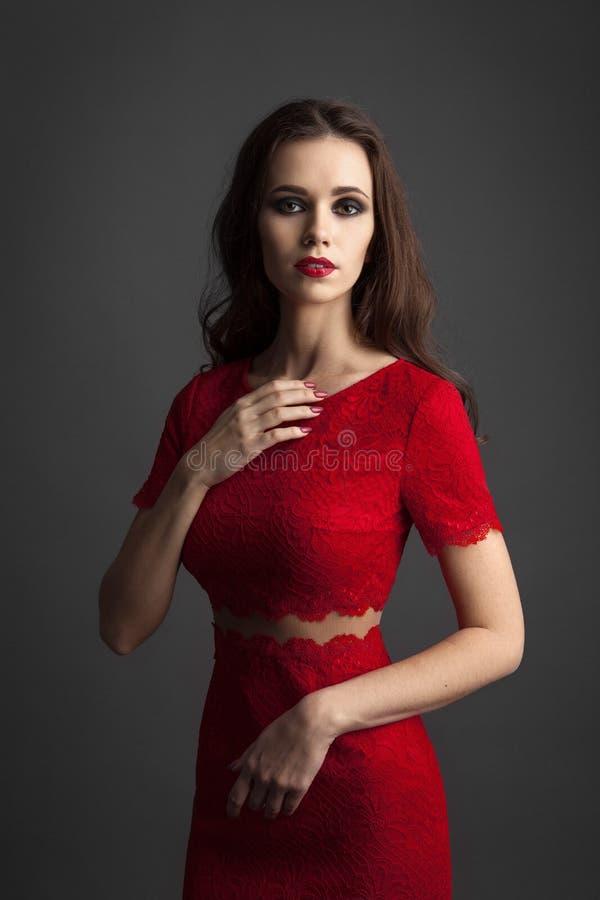 Recht junge sexy vorbildliche Frau mit dem dunklen Haar in erstaunlichem rotem Kleid lizenzfreies stockfoto