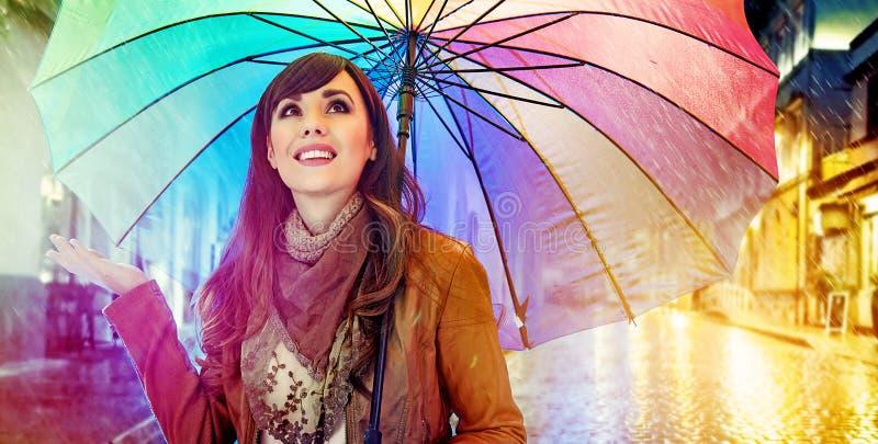 Recht junger Brunette, der das regnerische Wetter genießt stockbilder
