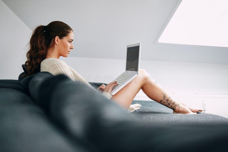 Recht junger Brunette, der zu Hause Laptop verwendet lizenzfreies stockfoto