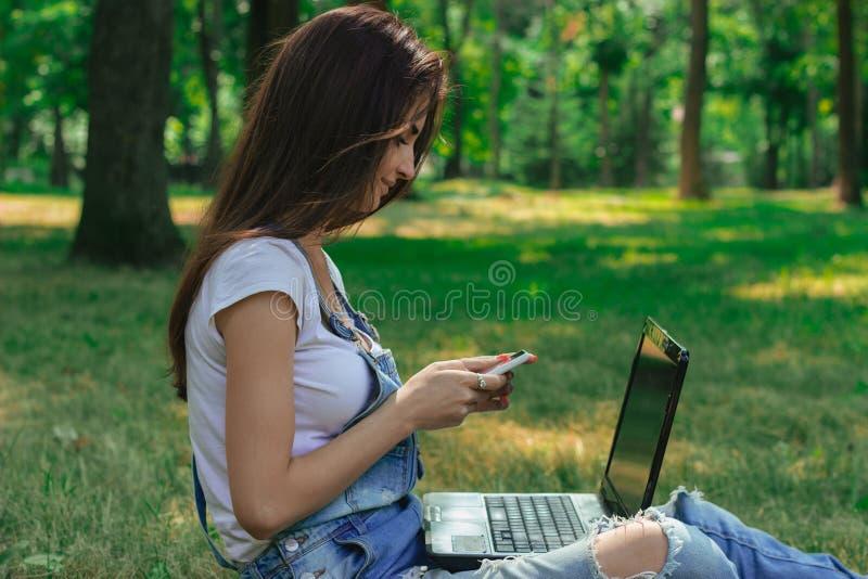 Recht junger Brunette mit Laptop unter Verwendung eines Handys lizenzfreies stockfoto
