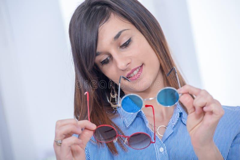 Recht junger Brunette wählt ein Paar Gläser lizenzfreies stockfoto