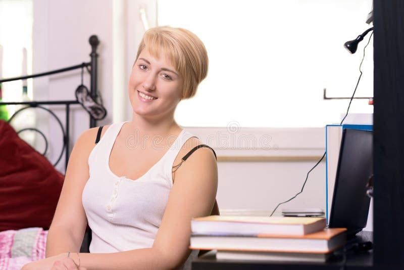 Recht junger Student, der in ihrem Schlafzimmer sitzt stockfotografie