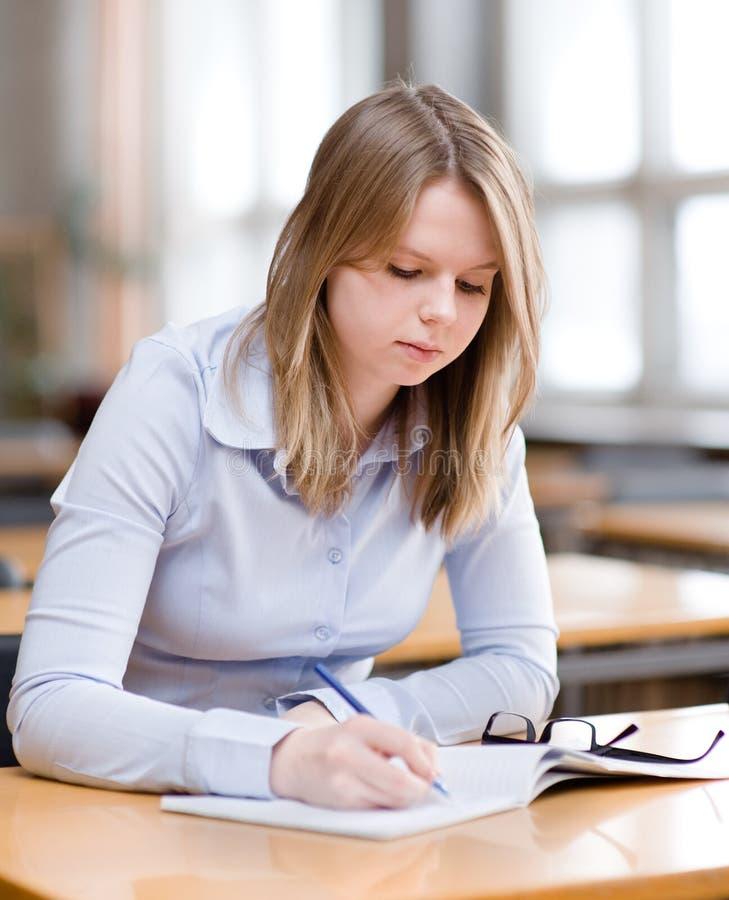 Recht junger Student in einer Bibliothek lizenzfreie stockfotografie