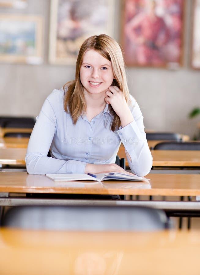 Recht junger Student in einer Bibliothek, die Kamera betrachtet lizenzfreie stockbilder