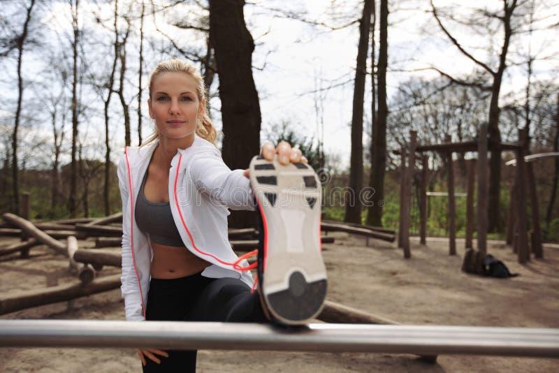 Recht junger weiblicher Athlet, der vor einem Lauf ausdehnt stockfotografie