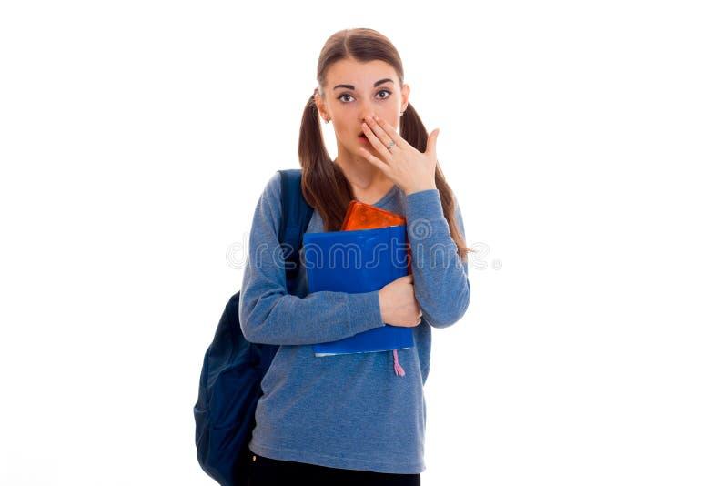 Recht junges Brunettestudentenmädchen mit dem blauen Rucksack lokalisiert auf weißem Hintergrund lizenzfreie stockbilder