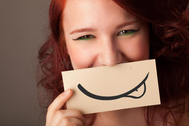 Recht junges Mädchen, das weiße Karte mit Lächelnzeichnung hält stockfotografie