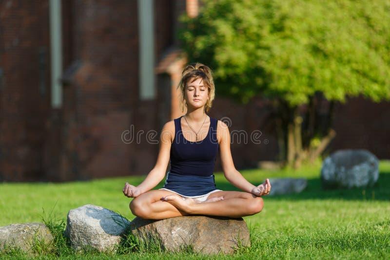 Recht junges Mädchen, das Yogaübungen tut stockfotografie