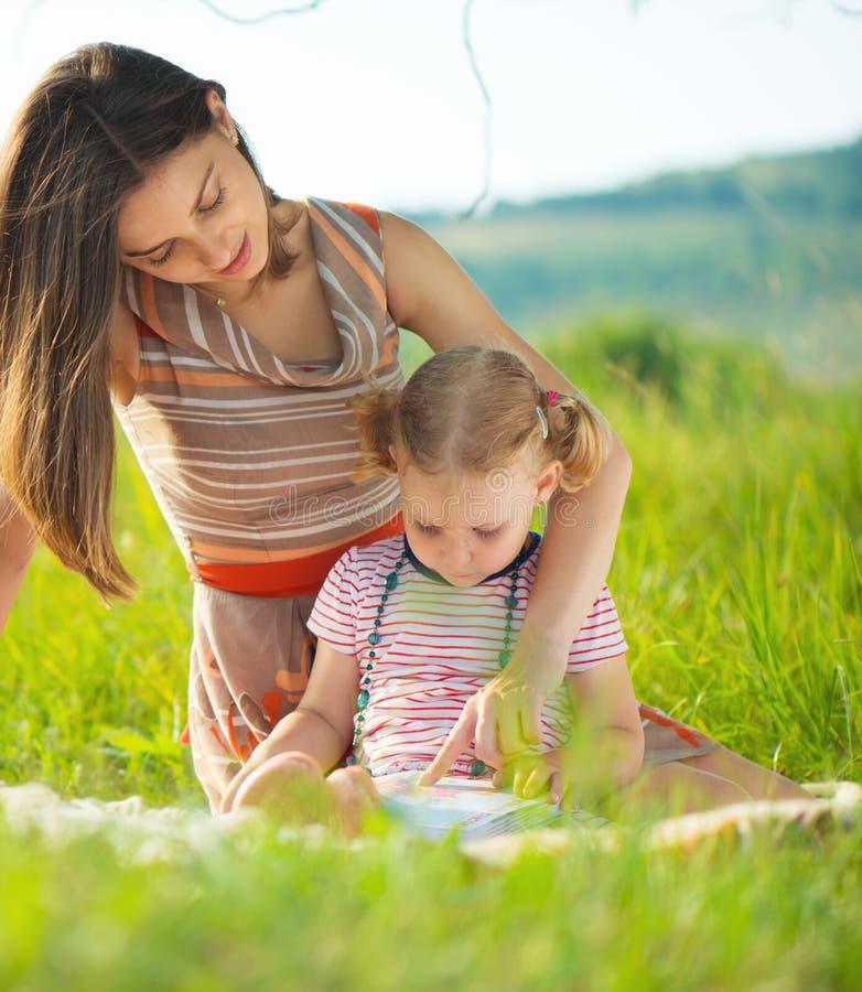 Recht junges Mutterlesebuch zu ihrer kleinen Tochter lizenzfreie stockfotografie