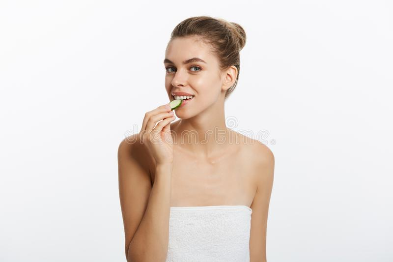 Recht junges natürliches Mädchen mit der perfekten sauberen Haut, die Kamera Gurkenscheibe über weißem Hintergrund essend betrach stockbilder