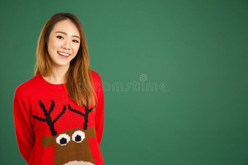 Recht junges singapurisches Mädchen tragender Weihnachtenpullover und smili lizenzfreie stockbilder