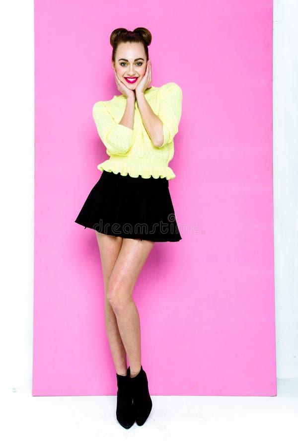 Recht junges spielerisches Mädchen kleidete im grünen Pullover und im Schwarzrock an lizenzfreie stockbilder