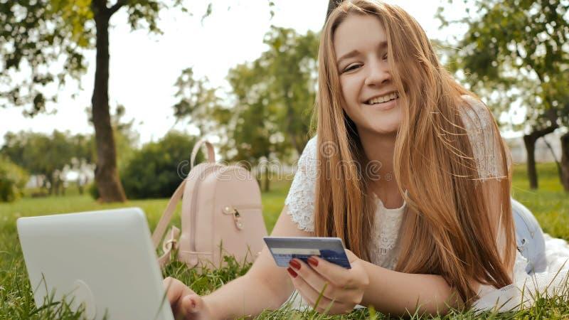 Recht junges Studentenmädchen schließt Käufe on-line unter Verwendung einer Kreditkarte und einer Laptop-Computers ab stockbilder