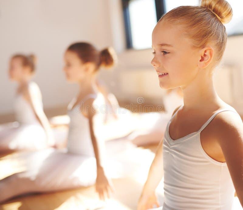 Recht kleine blonde Ballerina, die in der Klasse lächelt stockfotografie