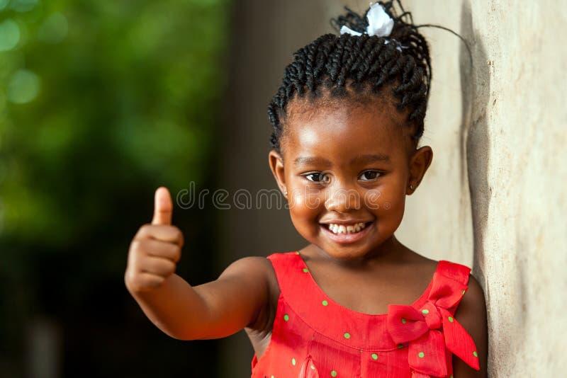 Recht kleines afrikanisches Mädchen, das sich Daumen zeigt. lizenzfreies stockfoto