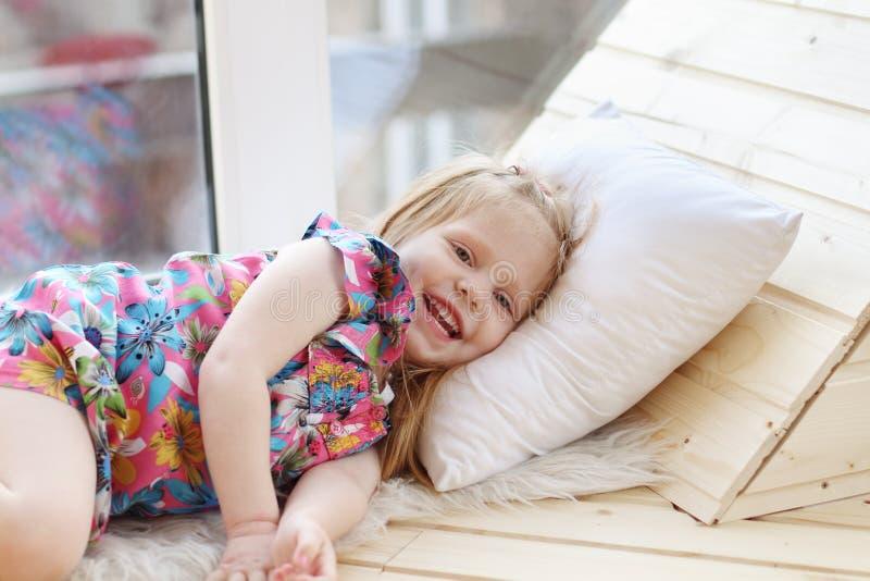 Recht kleines blondes Mädchen lacht und liegt auf weißem Kissen stockfotografie