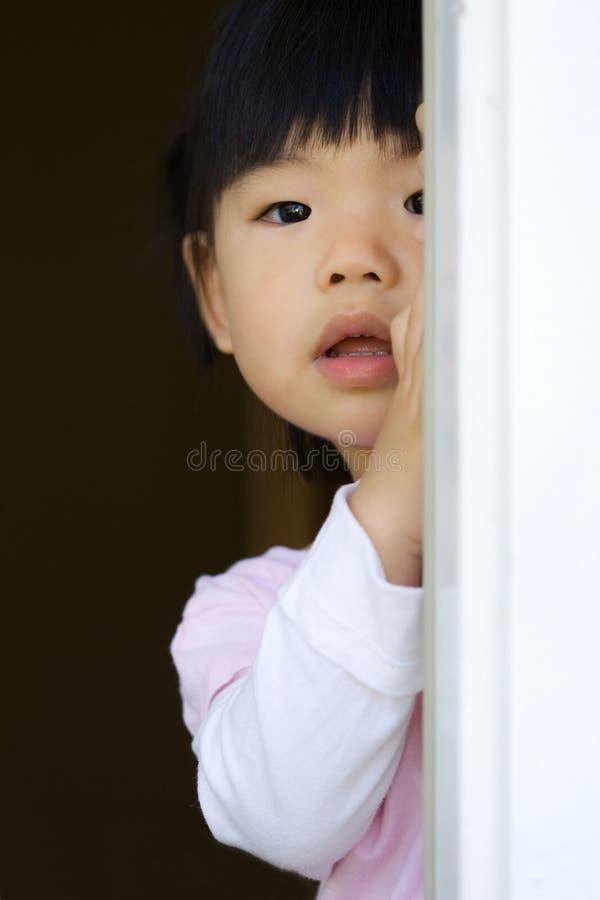 Recht kleines Kind steht hinter einer Tür stockbild
