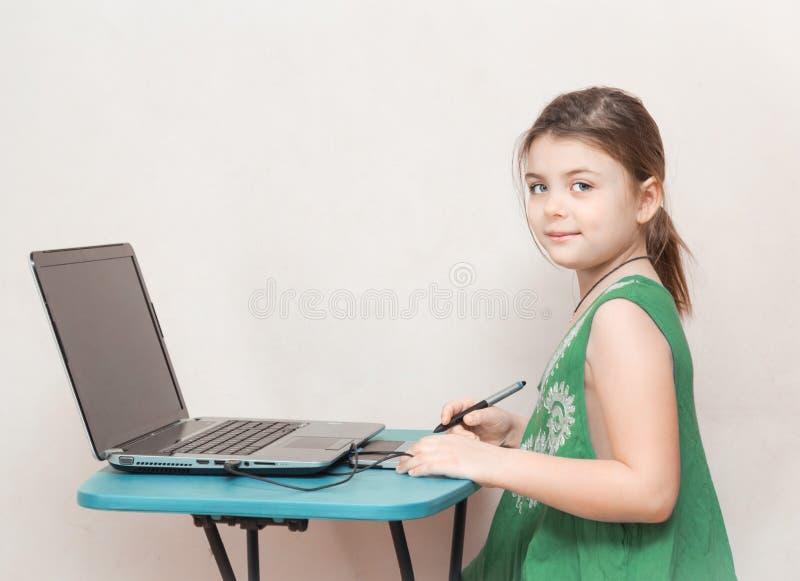 Recht kleines Mädchen, das hinter der Tabelle sitzt und an ihrem Notebook auf hellgrauem Hintergrund arbeitet lizenzfreie stockfotografie