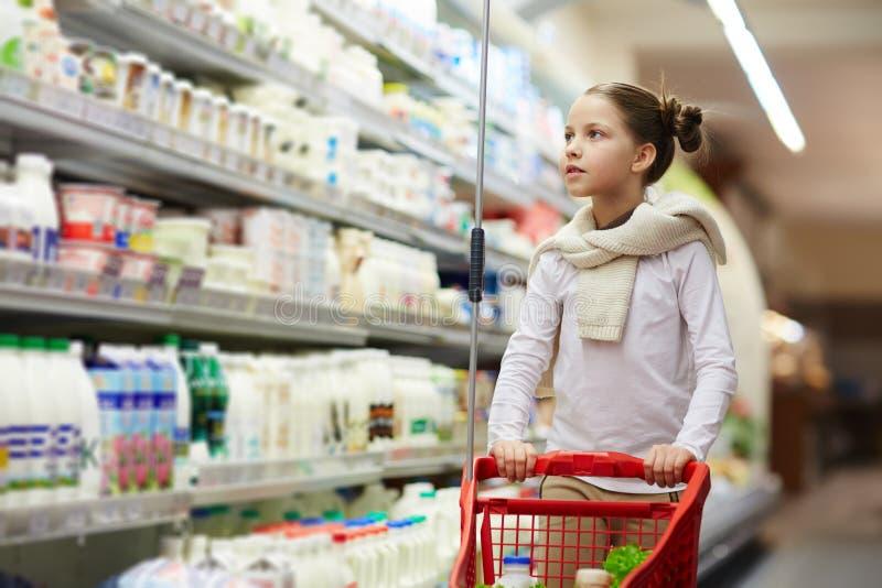 Recht kleines Mädchen, das kleinen Warenkorb im Supermarkt drückt lizenzfreies stockfoto