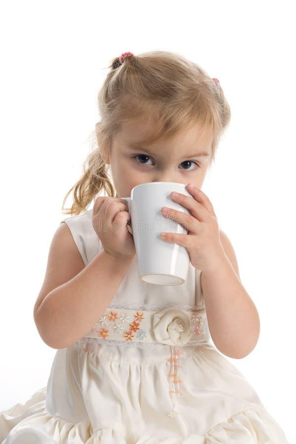 Recht kleines Mädchen, das vom weißen Cup trinkt stockbilder