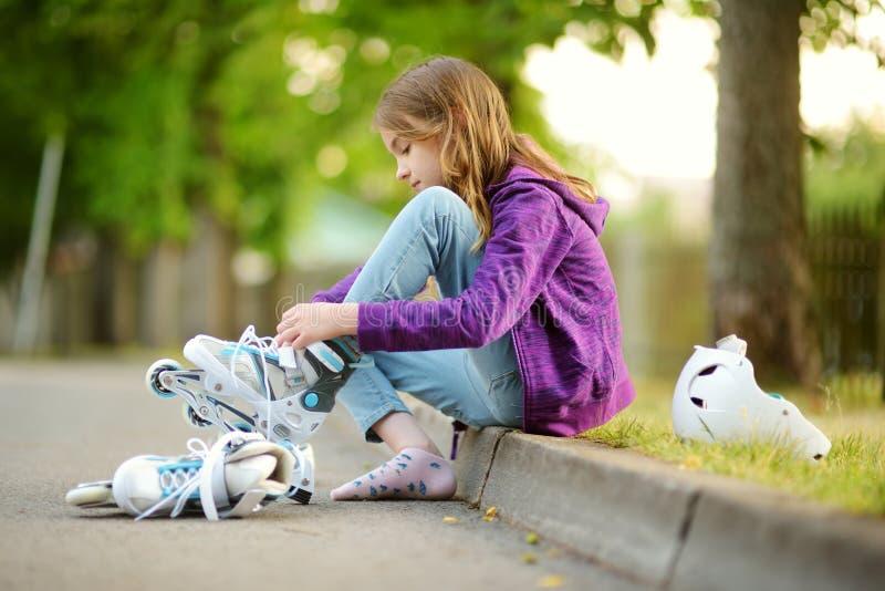 Recht kleines Mädchen, das zum Rollschuh am Sommertag in einem Park lernt Kinder-tragender Schutzhelm, der Rollschuhlaufenfahrt-o stockfotos