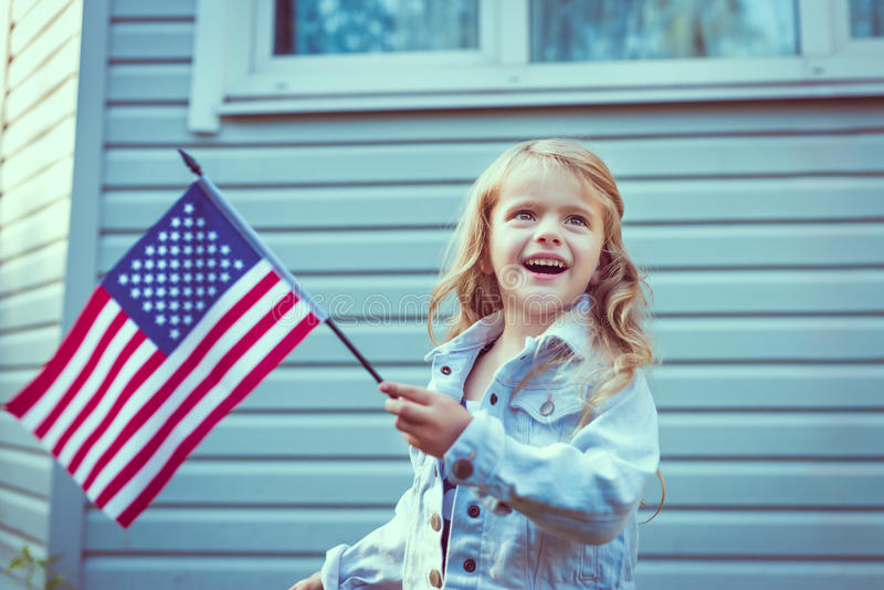 Recht kleines Mädchen mit dem langen gelockten blonden Haar lächelnd und wellenartig bewegend lizenzfreie stockbilder