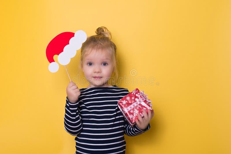 Recht kleines Mädchen mit Sankt-Hut und -Geschenkbox auf gelbem backgro lizenzfreie stockfotos