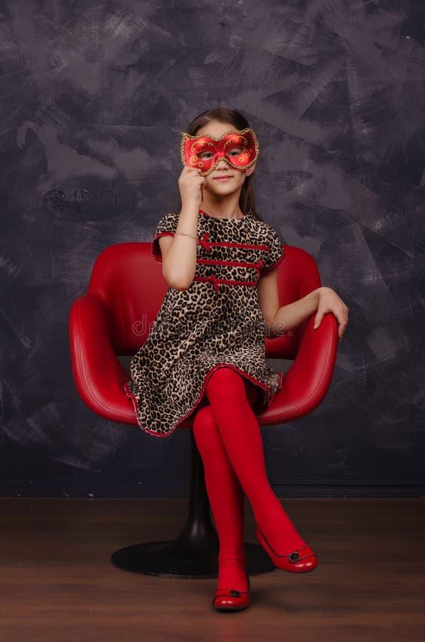 Recht kleines Mädchen, welches das schöne Kleid sitzt im roten Lehnsessel trägt Sie trägt rote Maskeradekarnevalsmaske Schönes Ta lizenzfreie stockbilder