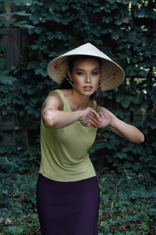 Recht koreanische Frau in einem dreieckigen Hut wirft auf lizenzfreies stockbild