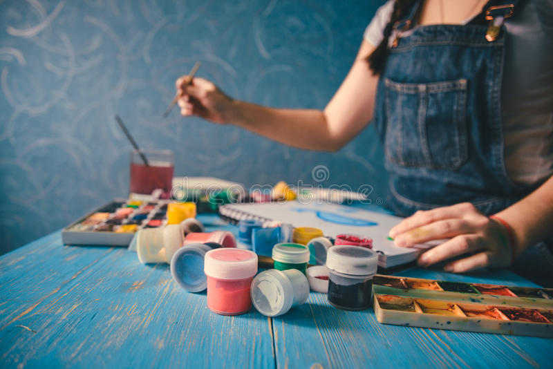 Recht lächelnde junge Frau, die ein Bild mit Plakatfarbe zeichnet lizenzfreie stockfotografie