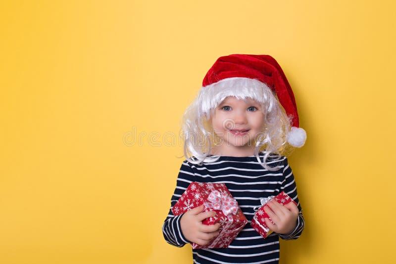 Recht lächelndes kleines Mädchen mit Sankt-Hut und -Geschenkbox auf yello lizenzfreie stockfotos