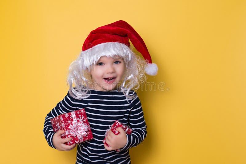 Recht lächelndes kleines Mädchen mit Sankt-Hut und -Geschenkbox auf yello lizenzfreie stockbilder