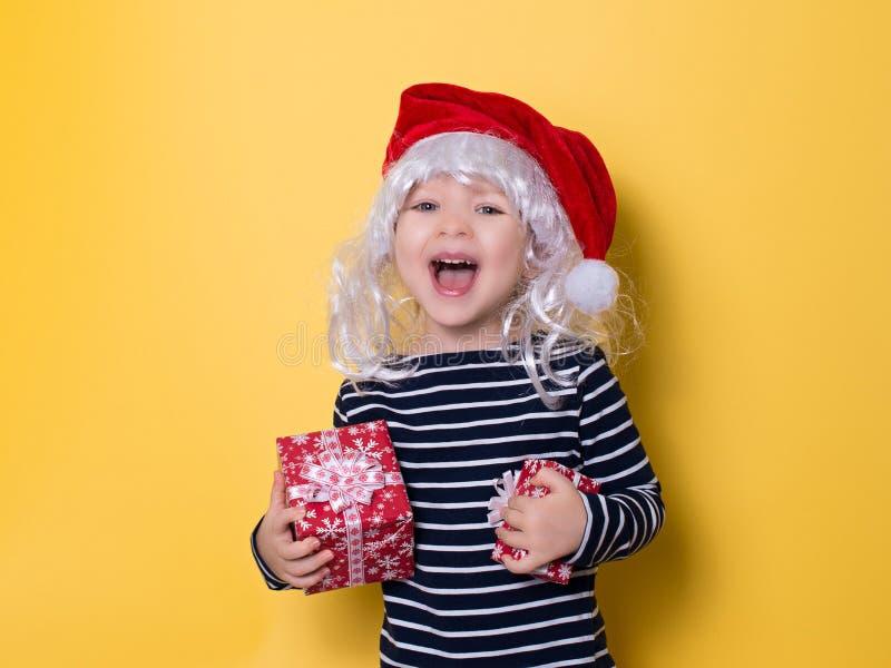 Recht lächelndes kleines Mädchen mit Sankt-Hut und -Geschenkbox auf yello stockbilder
