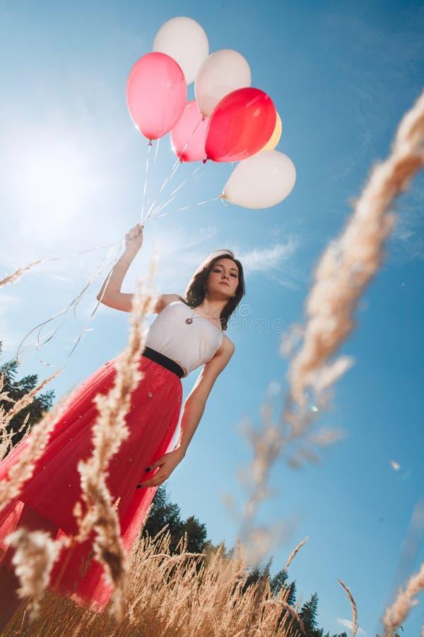 Recht Mädchen mit vielen farbigen Ballonen in der Hand lizenzfreie stockfotos