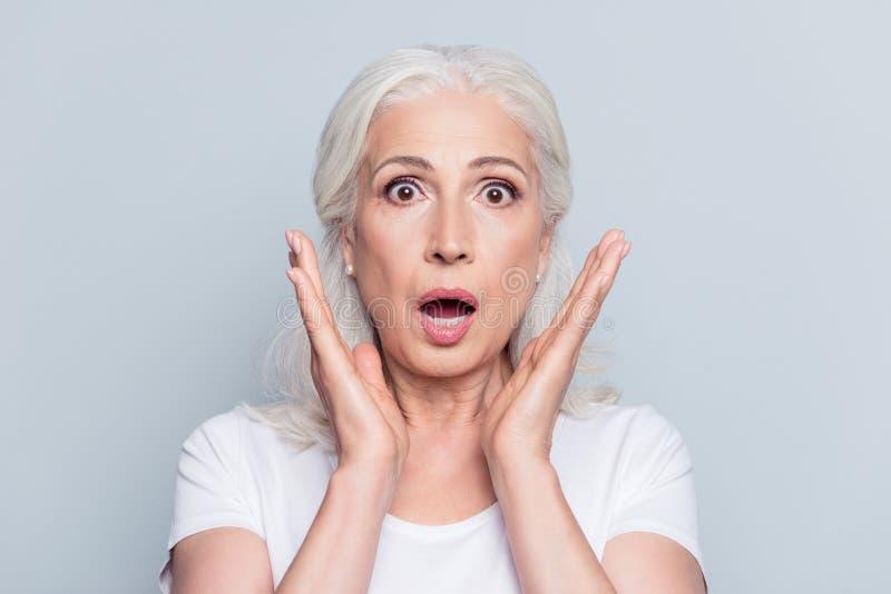 Recht nette, alte, entsetzte, erschrockene Frau mit weit geöffneten Augen und lizenzfreies stockfoto