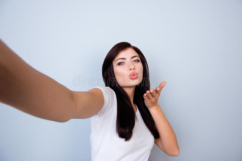 Recht positive nette junge Frau, die das selfie sendet Luft k macht stockfoto