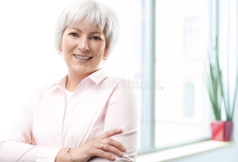 Recht reife Geschäftsfrau, die sicher lächelt lizenzfreies stockfoto