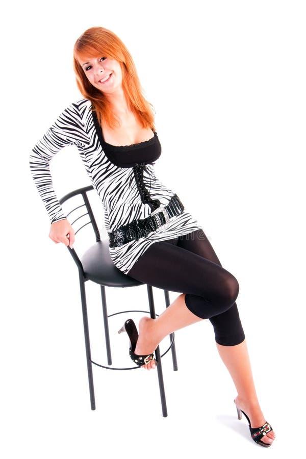 Recht reizend junges Mädchen im Kleid auf Stuhl stockfotografie