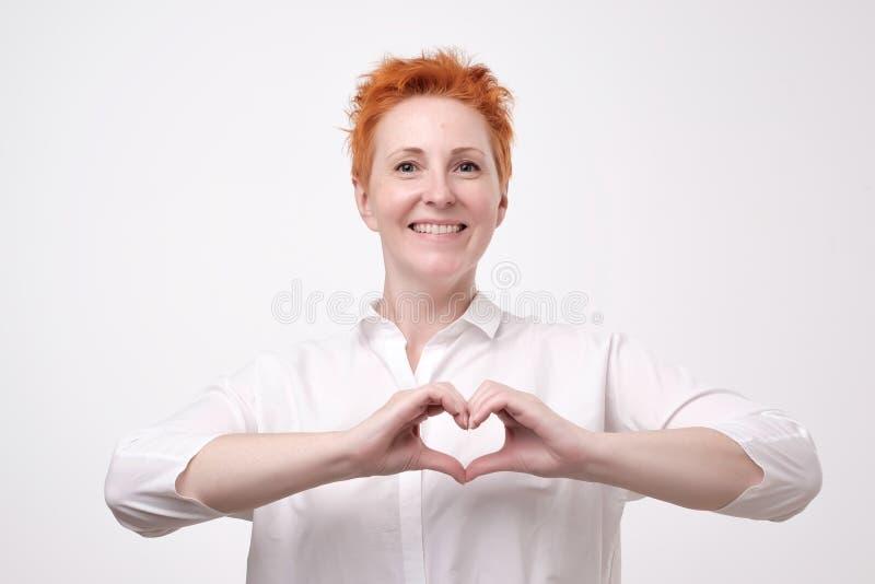 Recht romantische reife Rothaarigefrau, die eine Herzgeste mit ihren Fingern vor ihrem Kasten zeigt ihr Liebe macht stockbilder