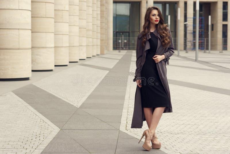 Recht schöne Geschäftsfrau im eleganten schwarzen Kleid lizenzfreie stockfotografie