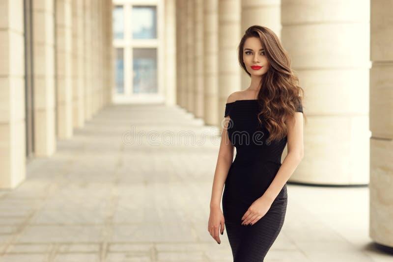 Recht schöne Geschäftsfrau im eleganten schwarzen Kleid stockfotografie