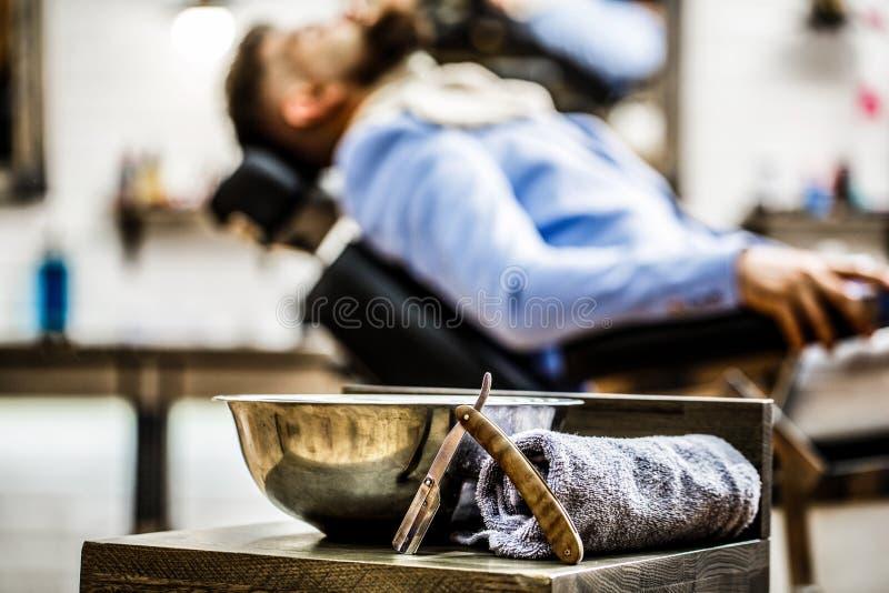 Recht scheermes, herenkapper, handdoek De salon van de kapperswinkel Mensenkapsel Mens in herenkappersalon Gebaarde mens, baard k stock fotografie