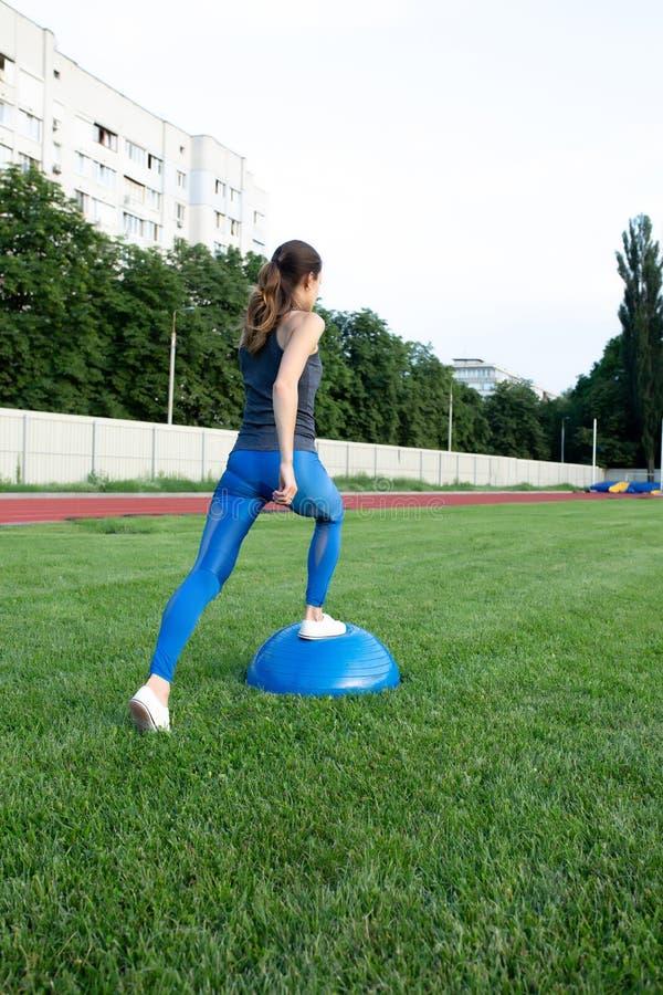 Recht schlankes Frauentraining mit bosu Ball am Stadion stockbild