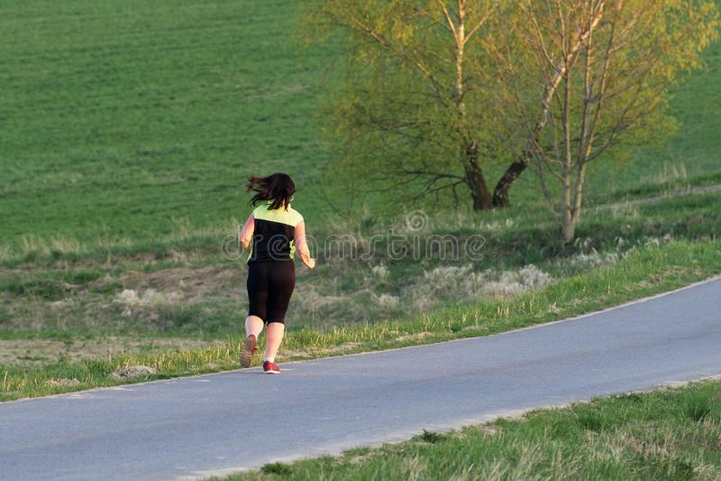 Recht sportliche Frau, die am Park im Sonnenaufgang rüttelt stockfoto