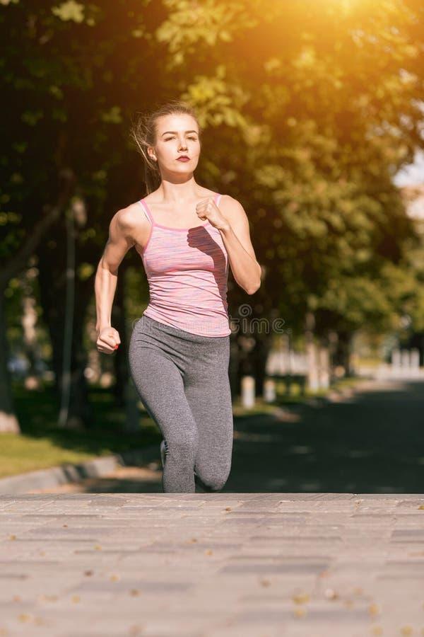 Recht sportliche Frau, die am Park im Sonnenaufganglicht rüttelt lizenzfreie stockfotografie