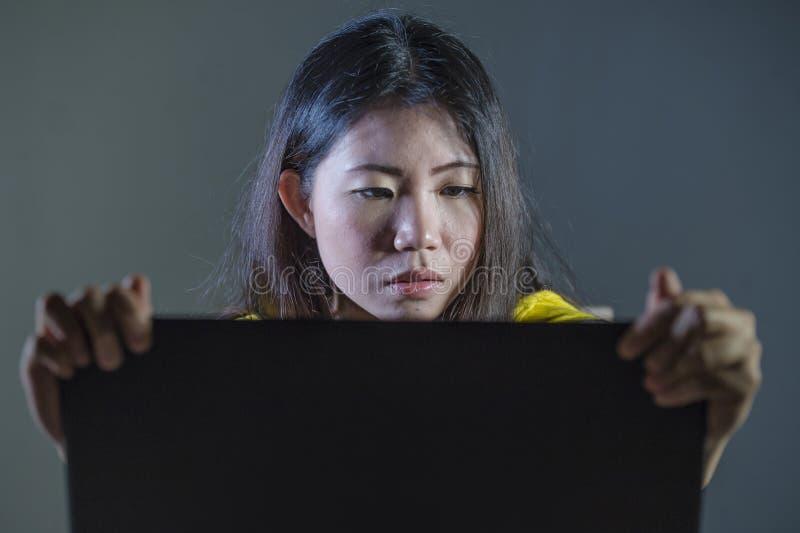 Recht starke und fokussierte Frau, die betontes und erschrockenes Aufpassen oder Ablesen etwas auf der Laptop-Computer hält Schir stockfoto