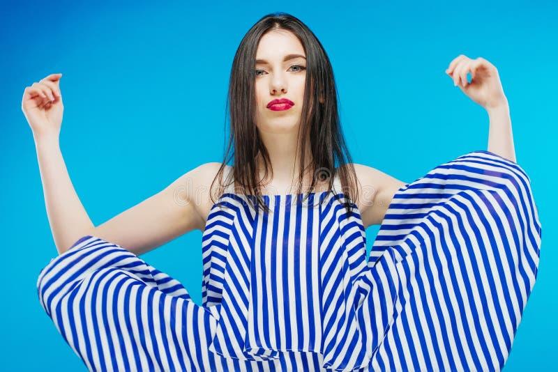 Recht stilvolles Mädchen mit dem langen Haar, das nobles schönes blaues Kleid trägt und gegen blauen Hintergrund aufwirft Mode Vo lizenzfreies stockbild