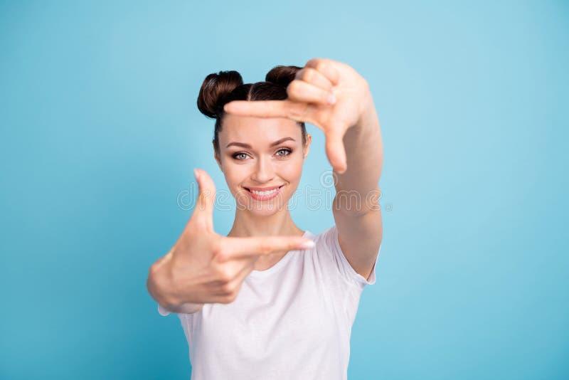 Recht tragen Dame, die eingebildeten Fotofokus mit den Händen macht, weißes zufälliges T-Shirt blauen hellen Hintergrund stockfoto